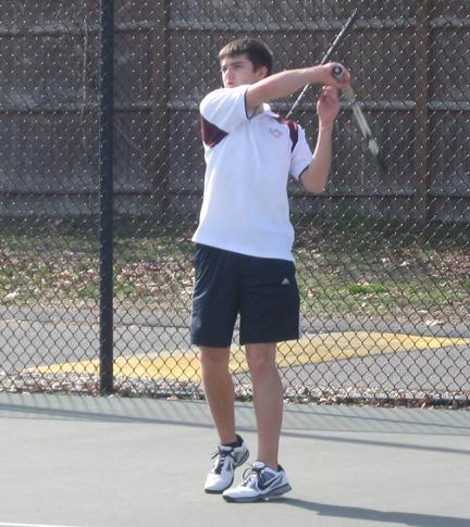 Sophomore Ian Dansereau returns a serve on the second singles court.