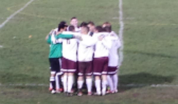 Senior boys cuddle before their second half on senior night.