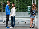 Teenage girl looking jealously at happy teenage couple waiting at bus stop
