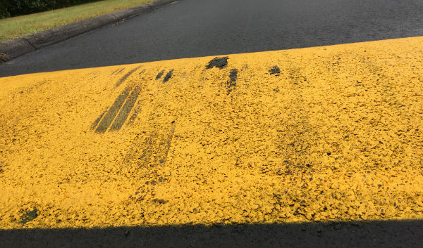 The second speed bump leading to the back student parking lot shows scrapes where the undercarriage of students' cars hit the surface,