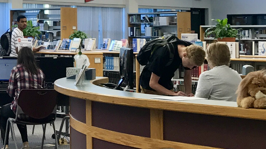 Senior Kyle Fortune signs in for a library pass before school.