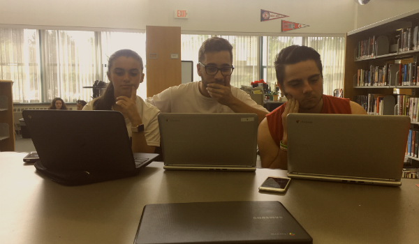 From left to right: sophomore Amanda Poirier, senior Matthew Goncalves, and senior Joe Banas use their newly issued Chromebooks in the Ludlow High School library.
