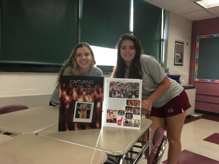 Seniors Kellie Salmond and Destiny Lavertue pose in front of last years yearbook
