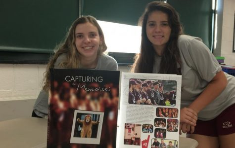 Seniors Kellie Salmond and Destiny Lavertue pose in front of last year's yearbook