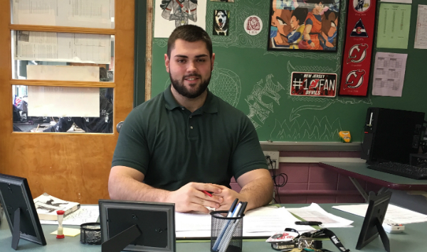 LHS 2013 graduate Ernad Minic sits behind his teacher's desk as a