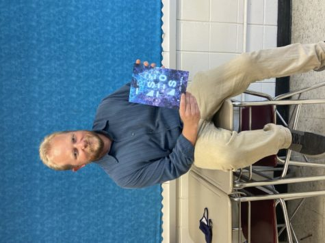 Dr, Johnson, English teacher, poses with his new book of poetry.